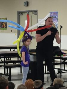 Man speaking, balloon animals, young girl
