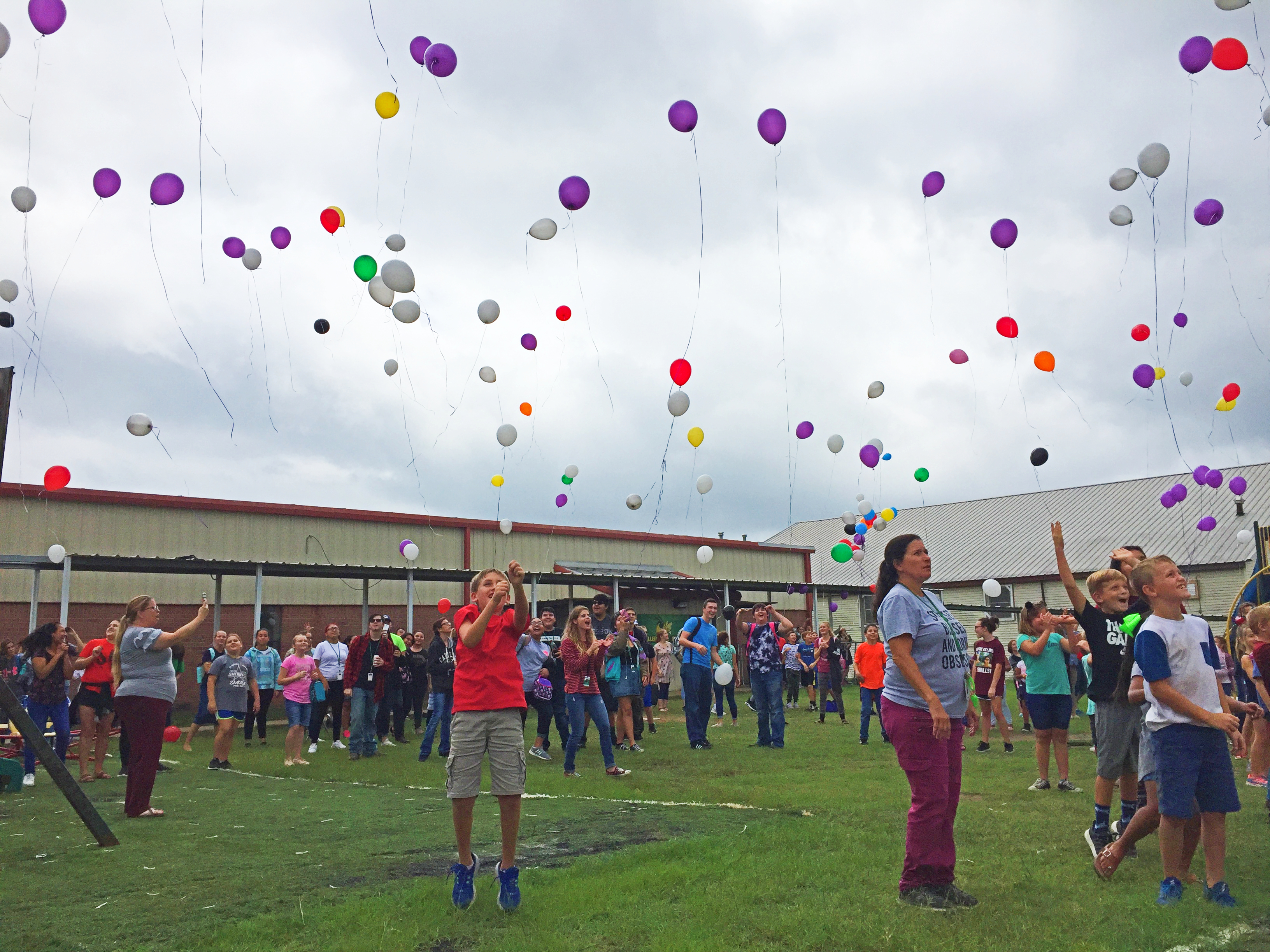 Students release balloons in memory of teacher