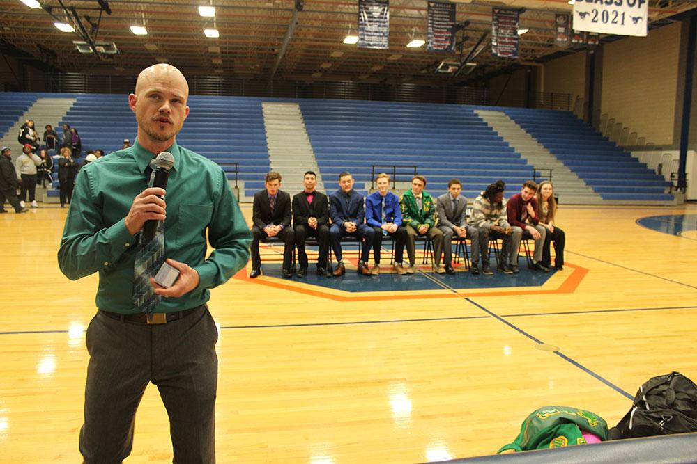 Coach speaks as seated team looks on